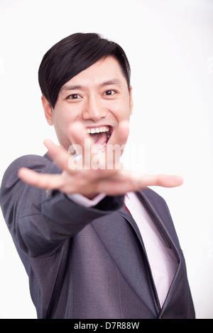 Young businessman reaching out towards camera, studio shot - Stock Photo