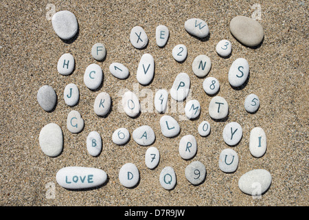 stones on a sand background, numbers and letters - Stock Photo