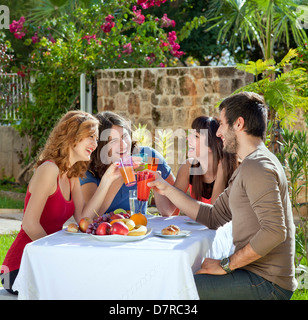 Couples enjoying a healthy outdoor lunch in the garden. - Stock Photo