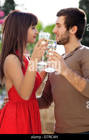 Romantic young couple dancing with glasses of white wine in their hands as they stare into each others eyes with - Stock Photo