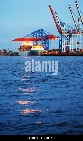 Image of container ship in the process of unloading in the harbor of Hamburg, Germany. - Stock Photo
