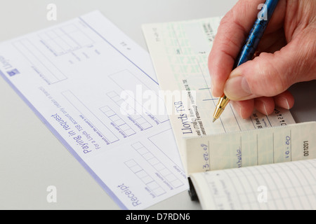 Woman pensioner saving money writing a Lloyds joint account cheque to pay in to a bank on a paying in credit slip. - Stock Photo