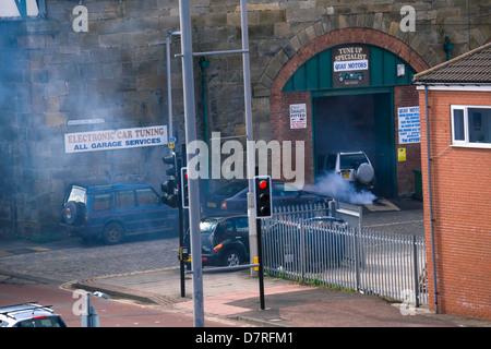 An old car emitting smoke at a garage. - Stock Photo