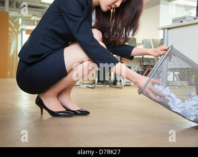 Young businesswoman looking through wastepaper bin in office - Stock Photo