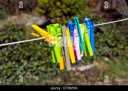 Colorful plastic pegs on washing line, washday - Stock Photo