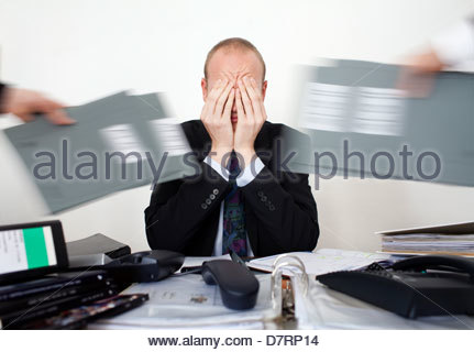 Businessman looking stressed with overload of work - Stock Photo