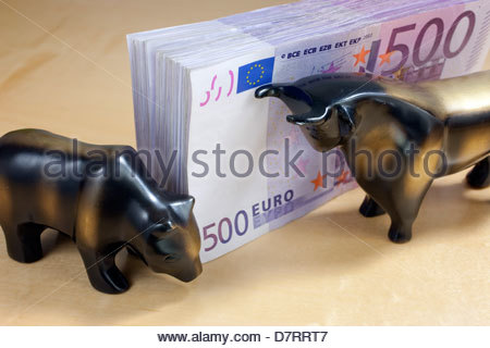 Close-up of a bundle of 500 euro notes with figurines of bear and bull - Stock Photo