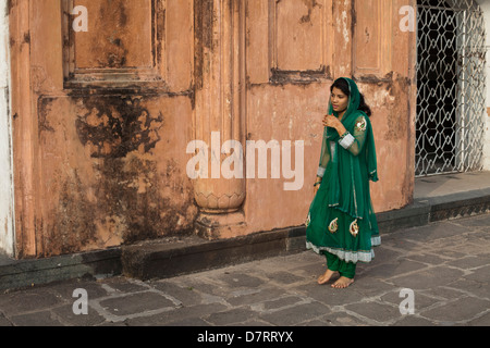 A young Muslim woman walks past the Tomb of Bibi Pari in Lalbagh Fort in Dhaka, Bangladesh - Stock Photo