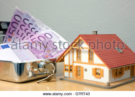 Close-up of a money box with five hundred euro notes near a model home - Stock Photo
