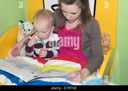 Young girl reading a story to a little boy. - Stock Photo