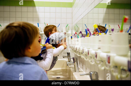 Michael Zawrel (L-R), Alba Aders und Benjamin Hewry clean their teeth at daycare centre 'Wichtel Akademie' in Munich, - Stock Photo