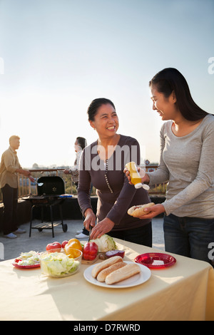 Mother and daughter preparing hot dogs for barbeque, father and son preparing sausages on barbeque - Stock Photo