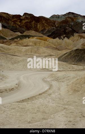 dirt track winds through Twenty Mule Team Canyon; Death Valley; California; USA - Stock Photo