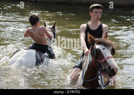 Boys riding horses in the river Eden during the Appleby Fair, an annual gathering of Gypsy and Traveller communities - Stock Photo
