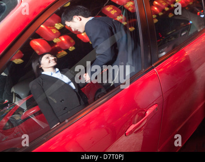 Coworkers handshaking next to the car at night, red lanterns on the background - Stock Photo