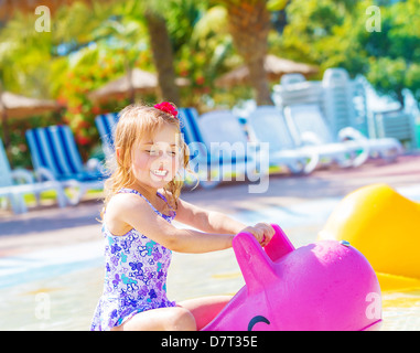 Happy baby girl having fun in aquapark, swimming in the pool on pink inflatable toy, daycare in summertime - Stock Photo
