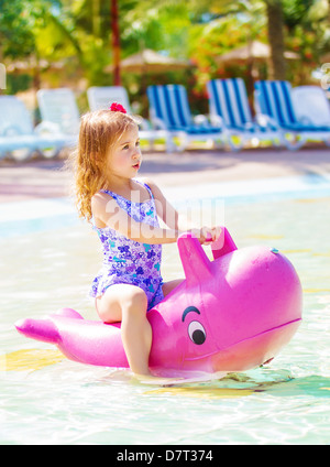 Cute little girl floating in aquapark, having fun in poolside in daycare, summer holidays, water attractions, happy - Stock Photo
