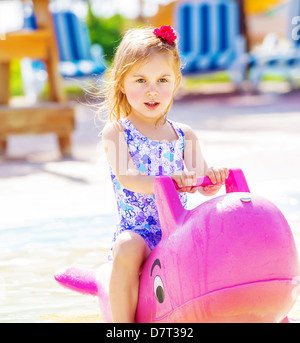 Closeup of active baby girl swimming in the pool on big pink inflatable dolphin, water attractions in child's camp - Stock Photo