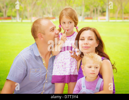 Portrait of happy family having fun outdoors, young parents with two cute kids in spring park, spending time together - Stock Photo