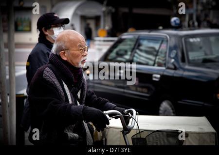 Cyclist and postman waiting at a junction, Ginza, Tokyo, Japan - Stock Photo