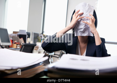 Young businesswoman sitting at desk covering her face with a paper - Stock Photo