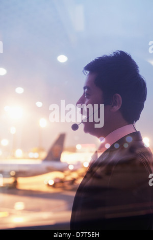 Double exposure of businessman with headset and airport - Stock Photo