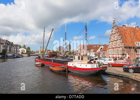 Leiden Holland barge and boats on the Rhine near the Morspoort (Marsh Gate), De Put windmill in background - Stock Photo