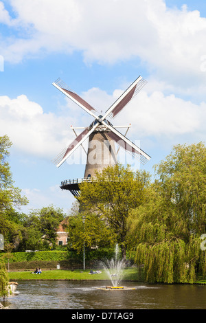 Leiden Holland, in spring - traditional Windmill museum De Valk on the River Oude with fountain and trees - Stock Photo