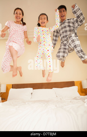 Family Jumping on Bed Together - Stock Photo