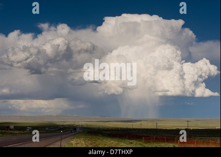 Cumulus clouds and virga (observable streak of precipitation that falls from a cloud). Interstate 80 by Rawlins, - Stock Photo
