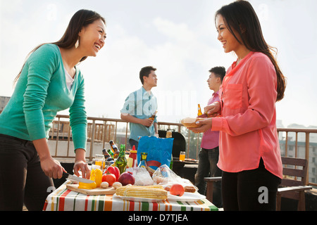 Group of Friends Having a Barbeque on a Rooftop - Stock Photo