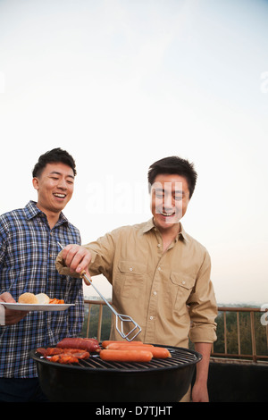 Friends Cooking Over a Grill - Stock Photo