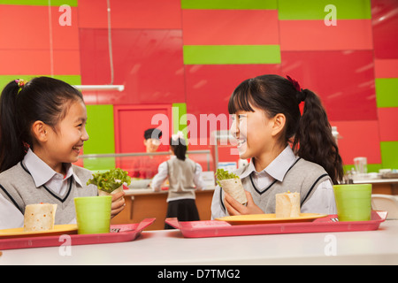 Two girls talking at lunch in school cafeteria - Stock Photo