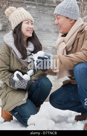 Couple Holding snow balls in park - Stock Photo