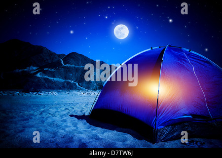 Camp on sandy beach, tent at the night with light inside, moon light, active tourism, hiking and traveling concept - Stock Photo
