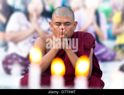 Buddhist monk praying at Shwedagon Paya (Shwedagon Pagoda), Yangon (Rangoon), Burma - Stock Photo