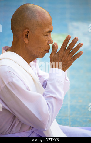Buddhist monk praying at Botataung Paya (Botataung Pagoda), Yangon (Rangoon), Burma - Stock Photo