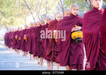 Buddhist monks walking along road to collect alms, near Shwezigon Paya, Nyaung U, Bagan, Burma - Stock Photo