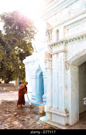 Buddhist monk cleaning paving outside a small temple near the famous U Bein teak bridge, Amarapura, near Mandalay, - Stock Photo