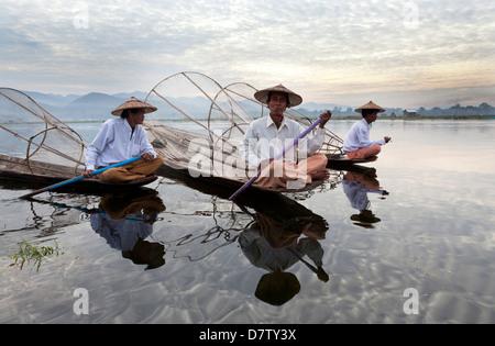 Intha leg rowing fishermen at sunset on Inle Lake, Inle Lake, Shan State, Burma - Stock Photo