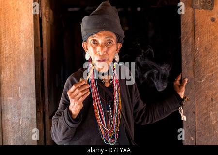 Woman of the Ann tribe in the doorway of her home in a hill village near Kengtung, Shan State, Burma - Stock Photo