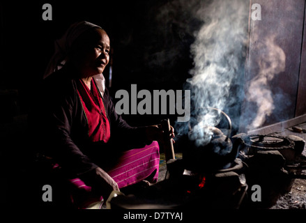 Woman of the Palaung tribe cooking on open fire in her home in village near Kengtung (Kyaingtong), Shan State, Burma - Stock Photo