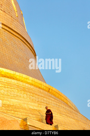 Buddhist monk walking around the gilded dome of Shwedagon Paya (Pagoda) at dusk, Yangon (Rangoon), Burma - Stock Photo