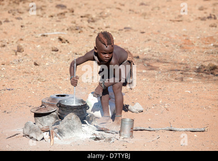 Young Himba boy cooking food on open fire in his village, Kunene Region (formerly Kaokoland) in the far north of - Stock Photo