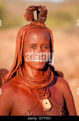 Himba woman inside a mud dwelling hut wearing dress and jewellery and covered in Otjize, Kunene Region, Kaokoland, - Stock Photo