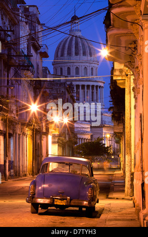 Vintage American car parked on floodlit street with The Capitolio in the background, predawn, Havana Centro, Cuba, - Stock Photo