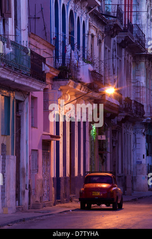 Vintage American car parked on floodlit street, predawn, Havana Centro, Cuba, West Indies - Stock Photo