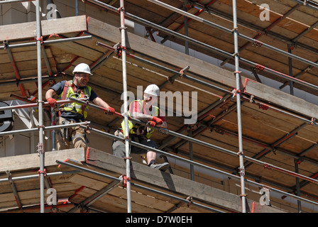 London, England, UK. Workmen looking down from scaffolding - Stock Photo