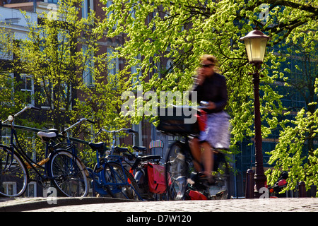 Cyclist on bridge over canal, Amsterdam, Netherlands - Stock Photo