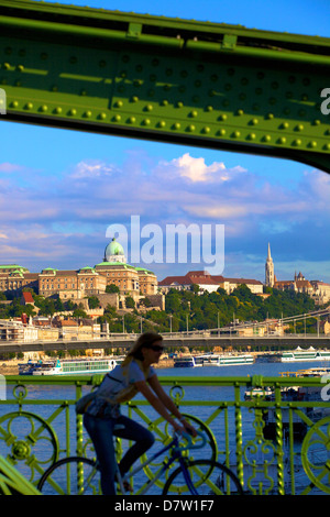 Cyclist on Liberty Bridge, Hungarian National Gallery in background, Budapest, Hungary - Stock Photo